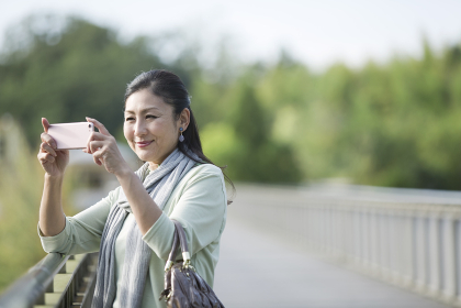 スマートフォンで写真を撮る中年女性