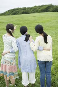 草原で腕を組む3人の女性の後姿