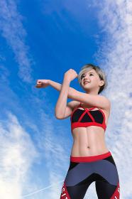 青い空を見上げながら準備運動をするショートヘアの女性