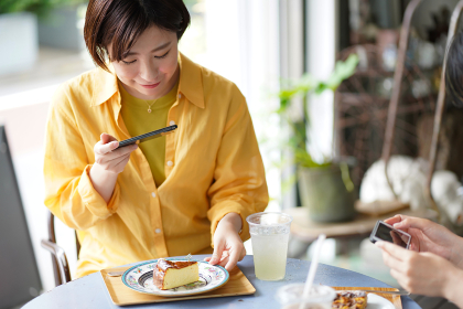 ケーキを持ち写真を撮る女性