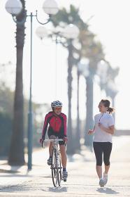 サイクリングとジョギングする女性