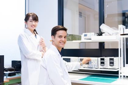 実験室で研究開発・解析・調査をする白衣の男性と女性(カメラ目線)