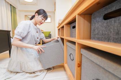 棚の片付けをする若い女性