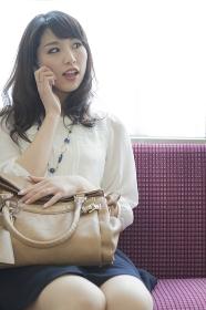 電車で電話をする女性