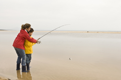 Mother teaching son to fish at beach