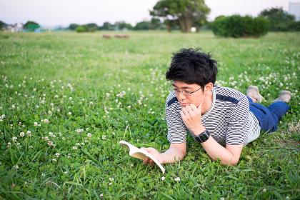 芝生の公園で本を読む男性
