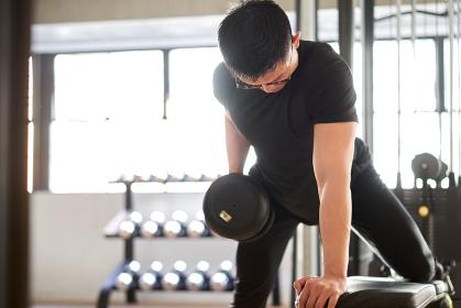 トレーニングジムでワンハンド・ベントオーバーロウをするアジア人男性