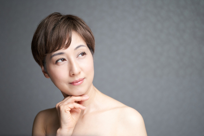 視線をそらし顎に手を当てる中年の日本人女性