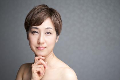 カメラ目線で顎に手を当てる中年の日本人女性