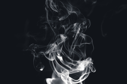 White smoke creating abstract shapes on a black background