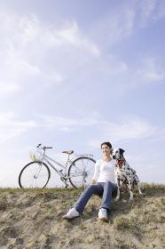 サイクリングの途中で愛犬と休憩する女性