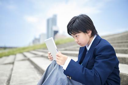 真剣にタブレットを見ている日本人男子中学生