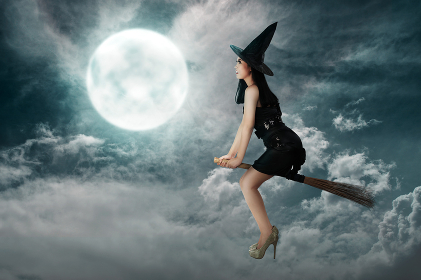 Happy asian witch woman flying above a broomstick