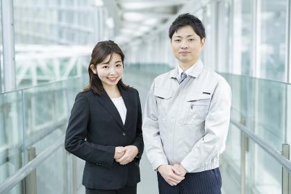 作業服姿のビジネスマンとスーツ姿のビジネスウーマン