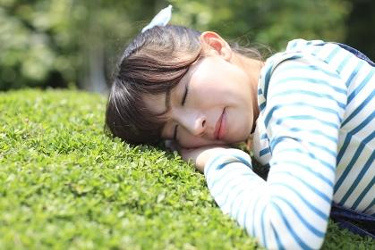 庭に寝転び寛ぐ女性