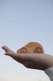 木製のおもちゃの車を持つ女性の手
