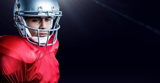 American football player wearing helmet standing against black background