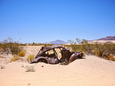 A rusted and abandoned car sits in a sand drift in the Mojave Desert.