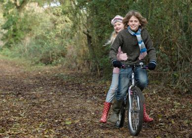 Boy and girl sharing bike in countryside