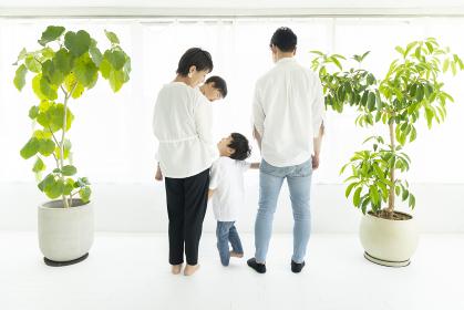 窓際に並んで立つ家族の背中