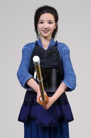 剣道の胴着をきて面を外した女の子が竹刀を握り笑顔で正面を向く