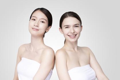 白いオフショルダーのトップスを着て並ぶコーカサス人とアジア人の若い女性