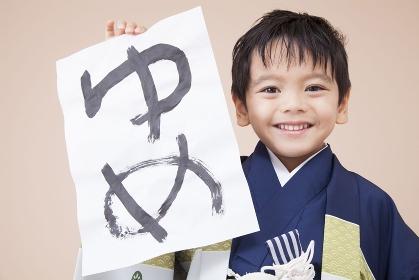 半紙を持って微笑む男児