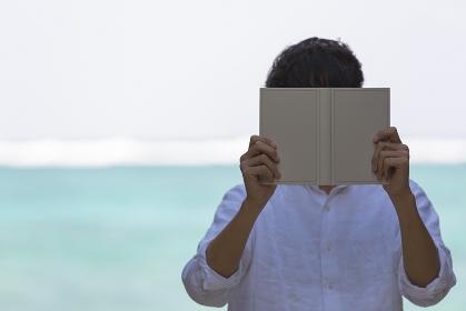 本で顔を隠す日本人男性