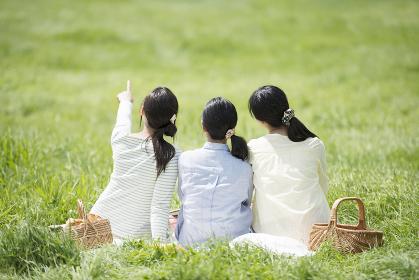 草原でピクニックをする3人の女性の後姿
