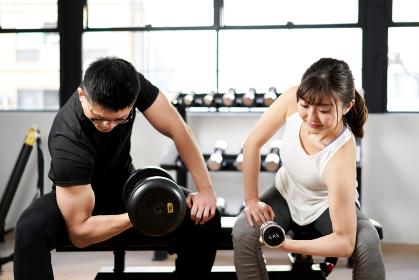 トレーニングジムでダンベルを持つアジア人の男女