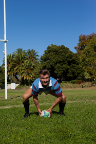 Portrait of rugby player crouching on field