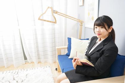スーツを着て読書をする女性