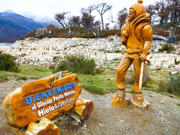 アルゼンチン・パタゴニア地方のペリトモレノ氷河にて氷山トレッキングをする男性木像と看板