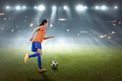 Young asian soccer player woman kick the ball