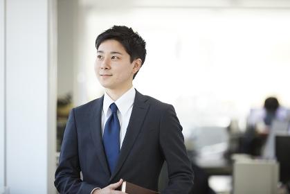 オフィスから外を眺める日本人サラリーマン