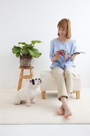 フレンチブルドッグと読書をする女性