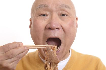 すき焼きを笑顔で食べるシニア