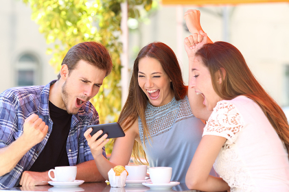 Excited friends celebrating good news watching phone content