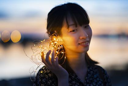 イルミネーションライトを耳に近づける若い女性