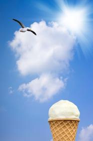 真夏の青空を飛ぶカモメと美味しそうなワッフルコーンに乗ったバニラアイスクリーム
