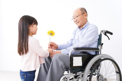 おじいちゃんにお花を渡す女の子