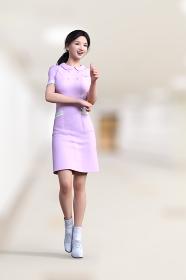 ピンクの看護服を着た日本人女性が片手の親指でグッドサインを出して病院の廊下でポーズをとる