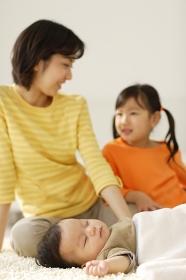 昼寝をする赤ちゃんを見守るお姉ちゃんとお母さん