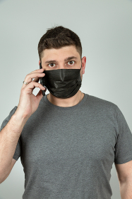 A man in a black medical mask on a gray background talks on the phone