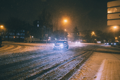 Cars driving carefully in snow covered roads during Filomena snowstorm in Madrid, Spain.
