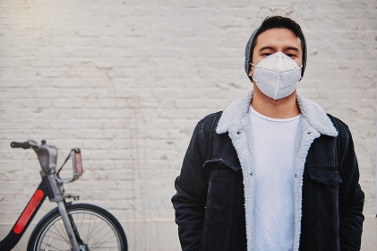 Young male in mask on city street