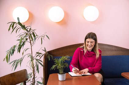 Smiling Millennial Taking Notes in a Colorful Cafe in Belgrade, Serbia , Serbia, Belgrade