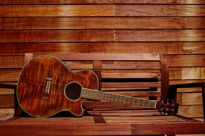 acoustic brown guitar in a wooden stripes wooden wall monochromatic