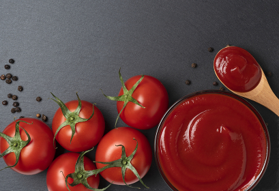 黒い石の背景とケチャップとトマトと黒胡椒