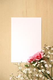 カーネーションとカスミソウの花束とカード 1 縦位置